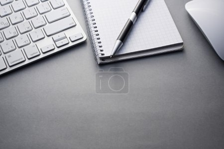 Keyboard, Mouse and Notebook with Pen on Grey Desk