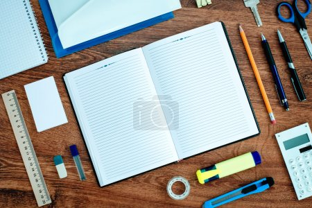 Photo for High Angle View of Office or School Supplies Neatly Organized Around Open Note Book with Blank Page on Wooden Desk Top - Royalty Free Image