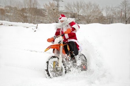 Santa Claus on a motorcycle rides through snowdrifts of snow with a feather of the rear wheel