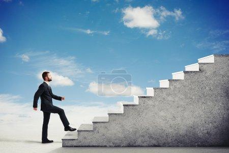 Photo pour Homme dans une tenue formelle escalade escalier en béton dans un ciel nuageux clair, vue latérale - image libre de droit