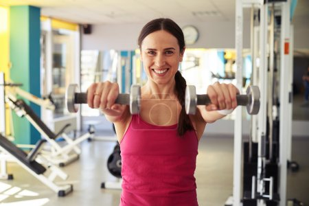 Woman is working out with dumbbells in gym