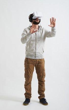 Photo pour Un jeune homme barbu en vêtements décontractés, écouteurs et lunettes de réalité virtuelle essaie de toucher quelque chose devant lui - image libre de droit