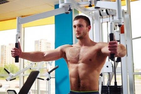 Man is working out chest muscles on the machine
