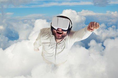 Photo pour Un jeune homme barbu en vêtements blancs porte des lunettes de réalité virtuelle et vole dans le ciel bleu parmi les nuages blancs - image libre de droit