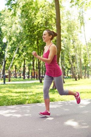 Graceful fit woman in skin-tight sportswear jogging in the park