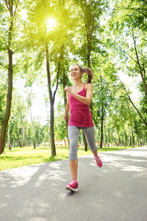 Graceful sporty woman jogging in the park