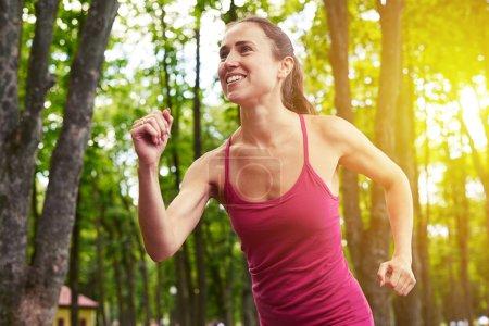 Photo pour Jeune femme sportive fait sa course matinale dans la forêt en profitant de l'air frais et belle nature - image libre de droit