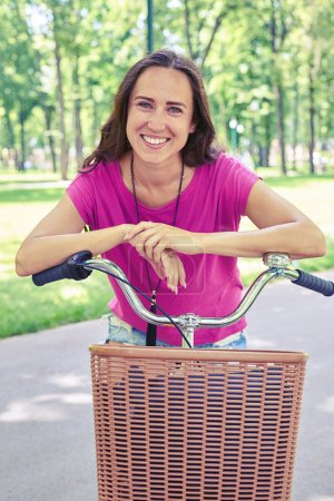 Close-up of beautiful female posing on bicycle in recreational a