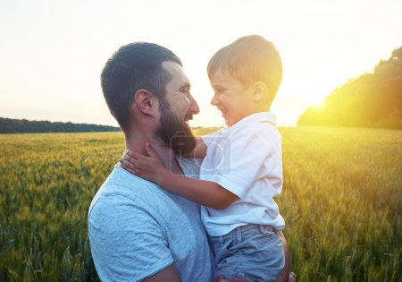 Photo for Father and his small son are looking at each other and smiling during magnificent sunset in the field - Royalty Free Image