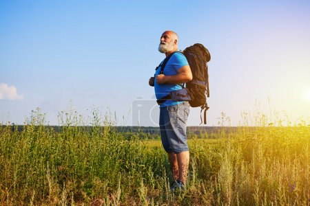 Aged man in good physical shape standing in the grass and carryi