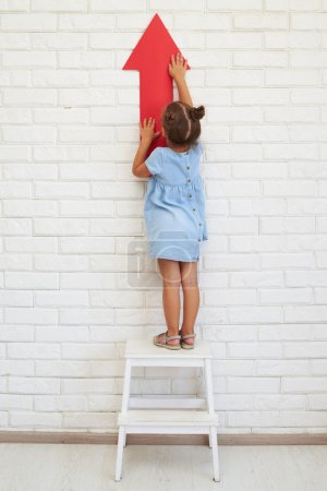 Photo for Little girl holds an arrow, standing on a chair, the concept of development and growing - Royalty Free Image