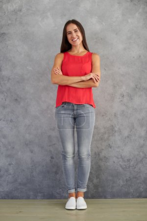 Young female in stylish casual wear standing against gray backgr