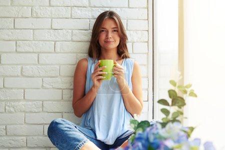 Photo pour Gros plan portrait d'une jeune fille enchantée assise sur le rebord de la fenêtre et tenant une tasse de café aromatique - image libre de droit