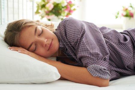 Photo pour Gros plan de charmante jeune femme rêvant dans son lit dans une chambre éclairée par le soleil - image libre de droit