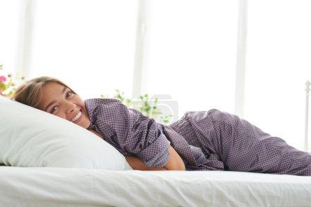 Portrait of beautiful girl in pajamas enjoying the morning lying