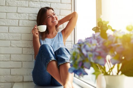Photo for The perfect morning relation with a cup of aroma coffee. Young girl in a casual stylish suit basking in the peaceful atmosphere. She looks calm, happy and relaxed while sitting on the window-sill. - Royalty Free Image