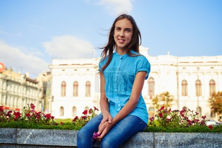 Dark-haired pretty teenage girl sitting on the street flowerbed