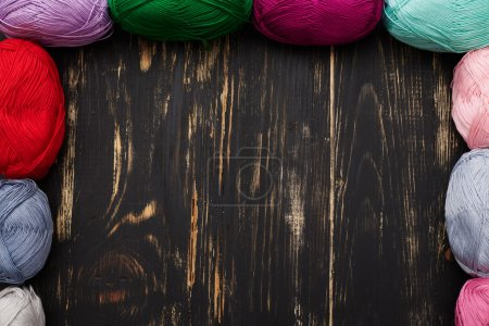 Photo for Top view of dark wooden table with empty space in the middle and skeins of different colors lying on sides - Royalty Free Image