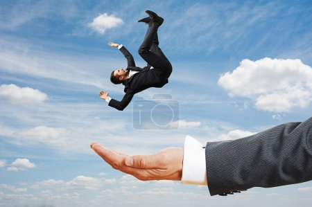 Photo for Big palm catching small frightened businessman over blue sky - Royalty Free Image