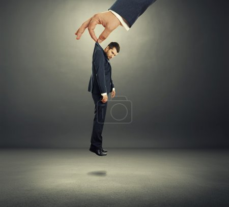 hand holding small discontented businessman