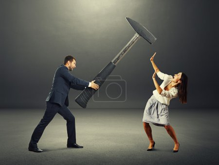 Photo for Angry screaming man holding big hammer and hitting scared woman. photo in the dark room - Royalty Free Image