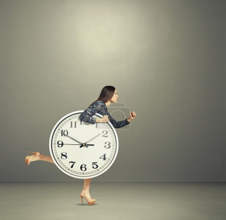 Photo for Serious woman holding big clock and running forward - Royalty Free Image