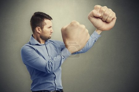 Photo for Funny picture of serious man with big fists over grey background - Royalty Free Image