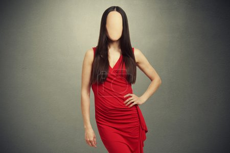 Photo for Attractive young woman in red dress with empty clear face posing over dark background - Royalty Free Image
