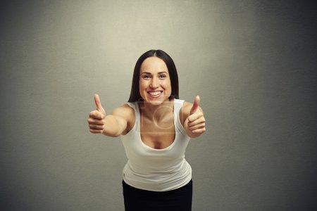 Photo pour Jeune femme souriante étirant vers l'avant et montrant les pouces vers le haut sur fond sombre - image libre de droit