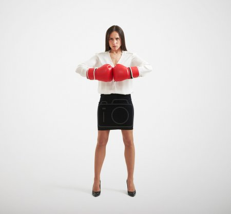 Photo for Full length portrait of confident businesswoman with red gloves looking at camera over light background - Royalty Free Image