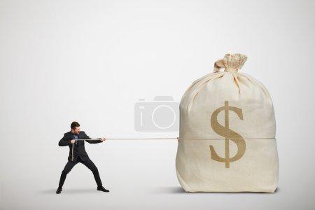 Photo pour Petit homme d'affaires tirant la corde un grand sac d'argent sur fond sombre - image libre de droit