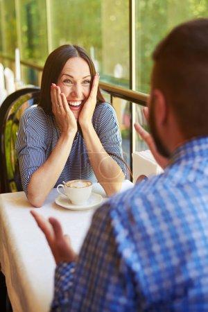 Photo pour Couple heureux aimant à la date au restaurant. jeune femme excitée riant et regardant l'homme gesticulant - image libre de droit