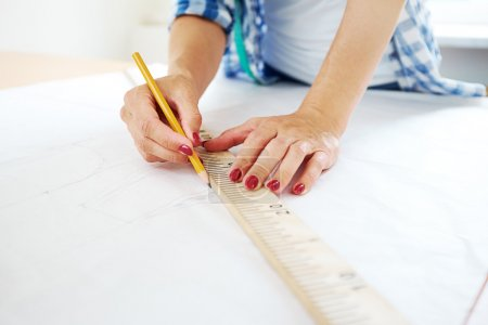 female hands with pencil and ruler