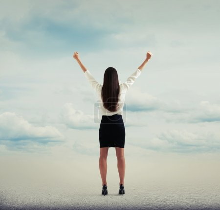 Photo for Back view of happy woman raising hands up over abstract background with clouds - Royalty Free Image