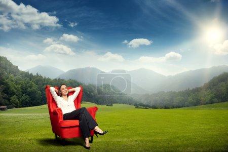 Photo pour Jeune femme souriante reposant dans une chaise rouge sur la prairie verte sur un beau paysage avec des collines, la forêt et le ciel - image libre de droit