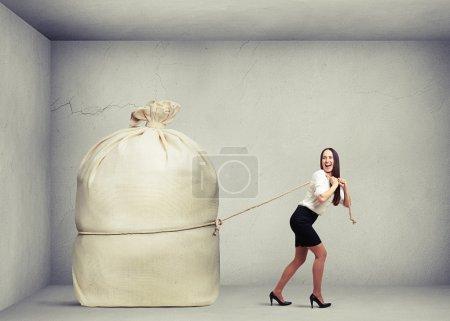 Photo pour Femme heureuse dans l'usure formelle tirant gros sac dans la salle de béton gris - image libre de droit