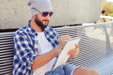 Photo for Smiley bearded man sitting on bench and writing in notepad at outdoors - Royalty Free Image
