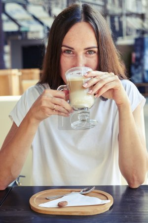 cheerful woman drinking cappuccino