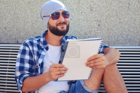 Photo pour Homme barbu souriant dans des lunettes de soleil assis sur le banc et tenant un bloc-notes blanc - image libre de droit