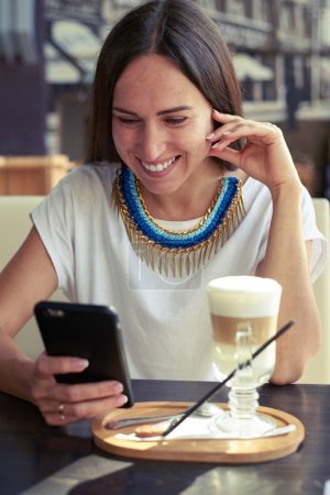 woman in cafe with smartphone