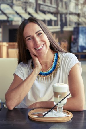 woman sitting in cafe with cappuccino