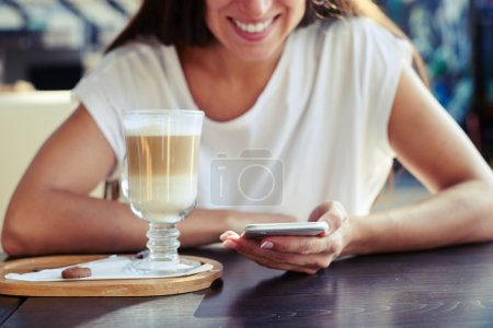 woman sitting in cafe with smartphone