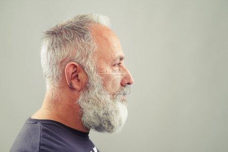 Senior bearded man over light grey background