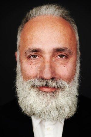 Smiley bearded senior man in formal wear
