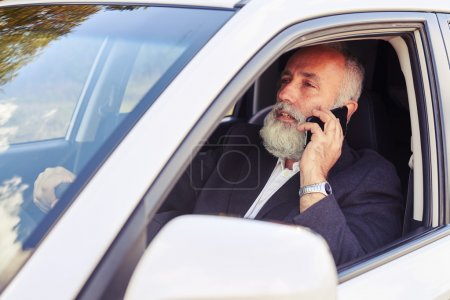man driving his car and talking on the phone