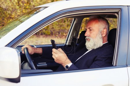 man driving his car and looking at smartphone