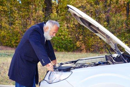 senior man looking under the hood of breakdown car