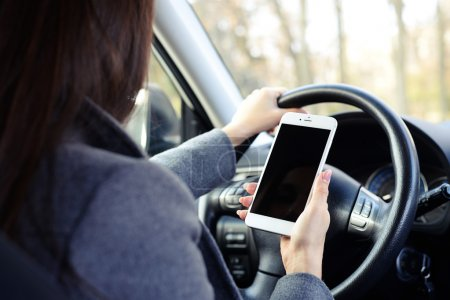 Photo for Back view of woman using smartphone and driving a car - Royalty Free Image