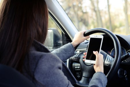 woman driving car and using smartphone