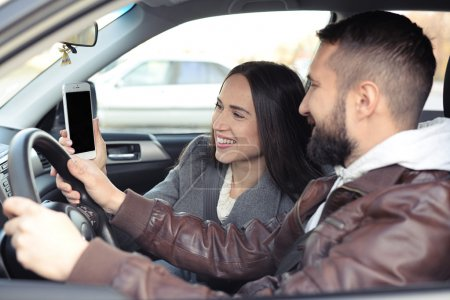 couple looking at smartphone in a car